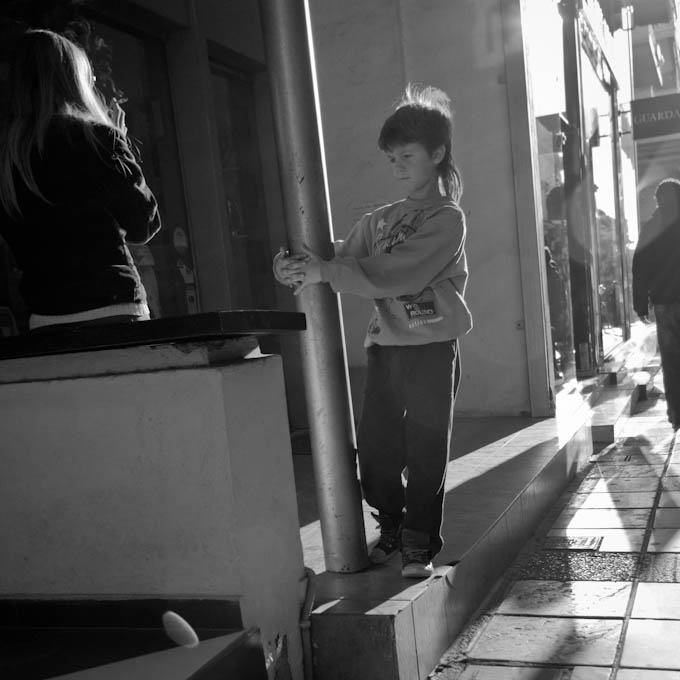 Boy playing next to a woman smoking, Kalamaria, Thessaloniki, Greece