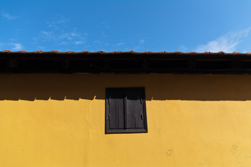 Yellow wall with window against blue sky at Paleos Panteleimonas, Greece