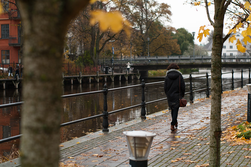 Woman walking by Fyris river at Uppsala, Sweden