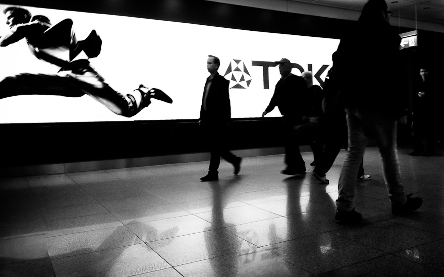 Man walking in front of TDK advertisement at Munich Airport, Germany