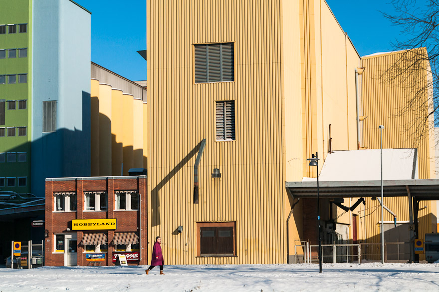 Woman walking in front of yellow building in upswUppsala, Sweden